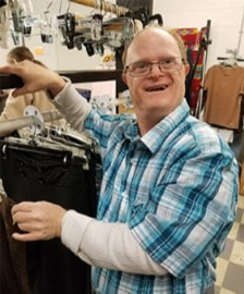 Donations Accepted link. Image of person served sorting donated clothing at resale store.